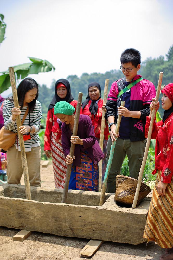 臼を用いた米搗き体験は、多くの観光客に好評です。