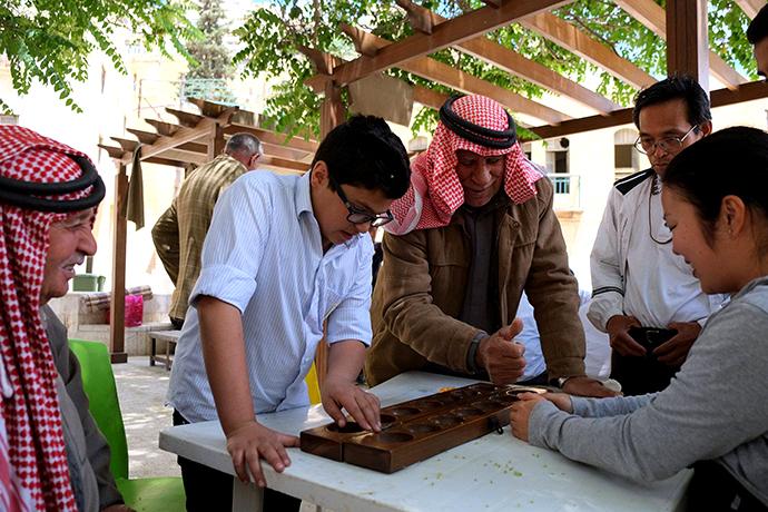 地元のおじいさん指導のもと、伝統的ボードゲームの「マンカラ」で遊ぶ