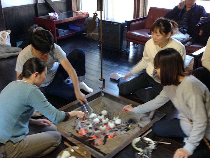 囲炉裏端で焼きおにぎりを焼く、中国からの旅行者